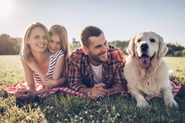 Family Laying On Grass With Dog