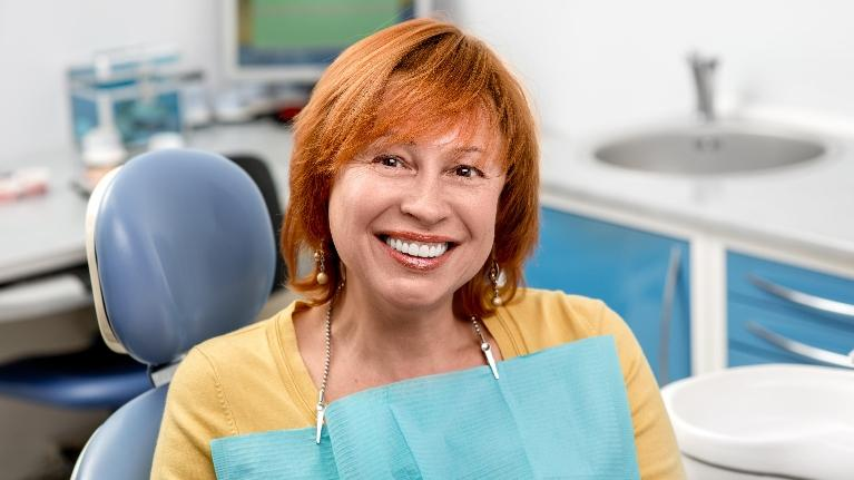A Woman Sits Smiling In The Dental Chair | Monroe Dentists